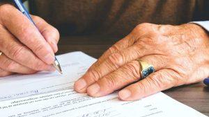 pessoa assinando documentos para reconhecimento de cidadania italiana